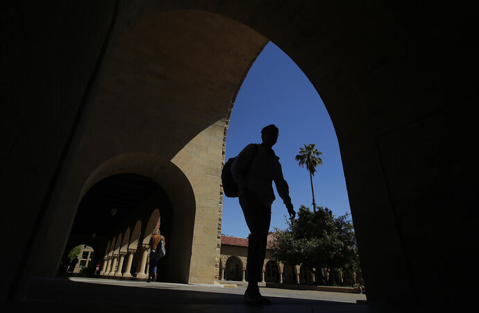 FILE - In this April 9, 2019, file photo, pedestrians walk on the campus at Stanford University in Stanford, Calif. Generally speaking, there are three types of award: free money, such as scholarships and grants; borrowed money, such as loans that need to be paid back; and earned money, such as work study in which you get a work-study job, earn the money and don't have to repay it. The offer will vary from year to year. (AP Photo/Jeff Chiu, File)