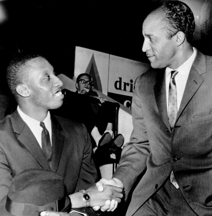 FILE - In this Dec. 22, 1961, file photo, Cleveland Pipers coach John McLendon, right, greets Dick Barnett, in Cleveland. When George Floyd died under the knee of a Minneapolis policeman, Harvard basketball coach Tommy Amaker knew it was time to get to work. Kentucky college basketball coach John Calipari and Harvard coach Tommy Amaker partnered on an internship program named for John McLendon, one of basketball's first black coaches. (AP Photo/File)