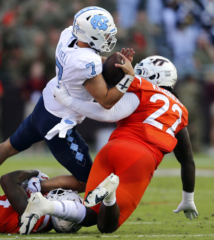North Carolina quarterback Sam Howell (7) is sacked by Virginia Tech's Chamarri Conner (22) during the first half of an NCAA college football game Friday, Sept. 3, 2021, in Blacksburg, Va. (Matt Gentry/The Roanoke Times via AP)