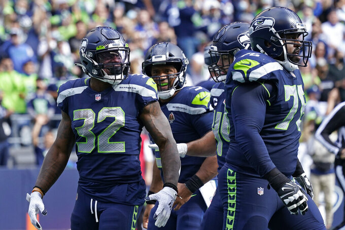 Seattle Seahawks running back Chris Carson (32) reacts after scoring a touchdown against the Tennessee Titans during the first half of an NFL football game, Sunday, Sept. 19, 2021, in Seattle. (AP Photo/Elaine Thompson)