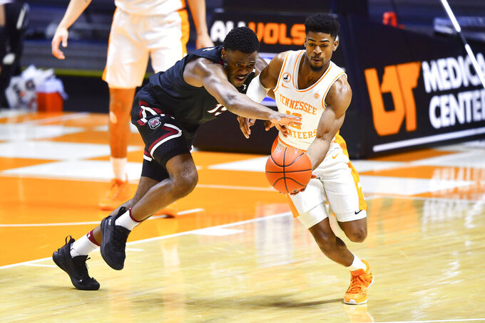 Tennessee's Victor Bailey Jr., right, and South Carolina's Wildens Leveque, left, vie for the ball during an NCAA college basketball game Wednesday, Feb. 17, 2021, in Knoxville, Tenn. (Brianna Paciorka/Knoxville News Sentinel via AP, Pool)