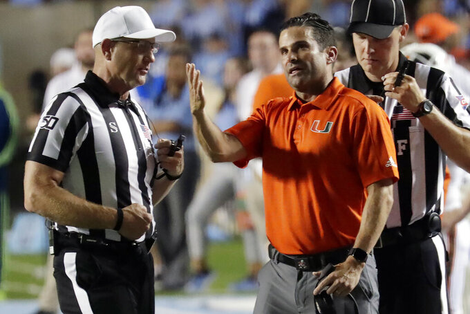 Miami coach Manny Diaz argues a call with an official during the first quarter of the team's NCAA college football game against North Carolina in Chapel Hill, N.C., Saturday, Sept. 7, 2019. (AP Photo/Chris Seward)