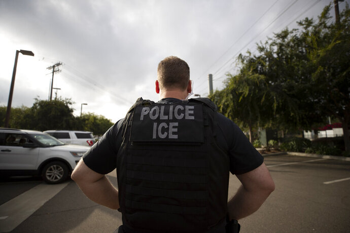 FILE - In this July 8, 2019, file photo, a U.S. Immigration and Customs Enforcement (ICE) officer looks on during an operation in Escondido, Calif. Advocacy groups and unions are pressuring Marriott, MGM and others not to house migrants who have been arrested by U.S. Immigration and Customs Enforcement agents. But the U.S. government says it sometimes needs bed space, and if hotels don't help it might have to split up families. (AP Photo/Gregory Bull, File)
