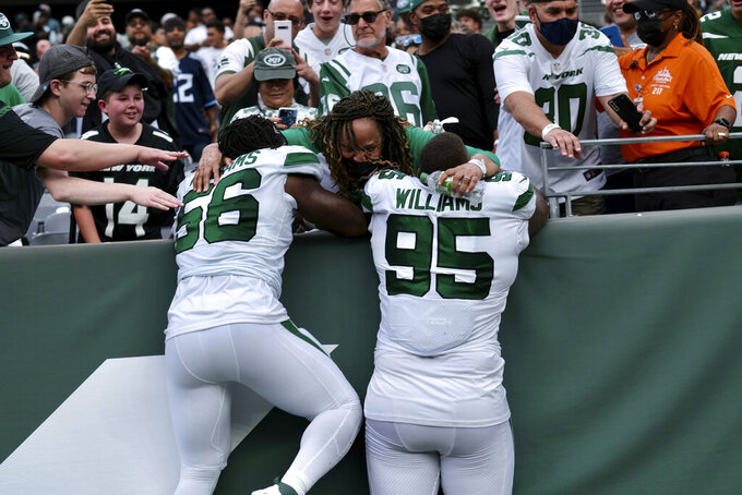 This photo provided by the New York Jets shows New York Jets NFL football players and brothers Quincy Williams (56) and Quinnen Williams (95) hugging their grandmother, Yvarta Henderson, at MetLife Stadium in East Rutherford, N.J., on Sunday, Oct. 3, 2021. Brothers Quinnen and Quincy Williams have become leading spokesmen for the NFL's annual Crucial Catch initiative. Their mother, Marquischa Henderson Williams, passed away when Quinnen was 12 years old after losing her second battle with breast cancer. (New York Jets via AP)