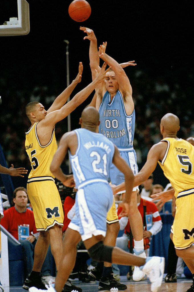 FILE - In this April 5, 1993, file photo, North Carolina's Eric Montross (00) flips a pass over to teammate Donald Williams (21) as Michigan's Juwan Howard covers during the first half of their Final Four NCAA championship game in New Orleans. North Carolina beat Michigan 77-71. (AP Photo/Paul Sancya, File)