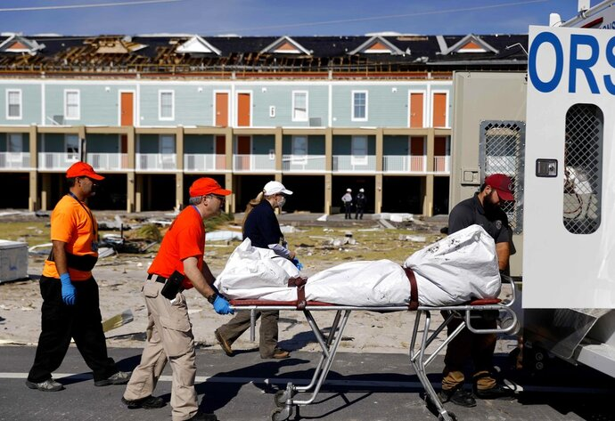 A body is removed after being discovered during the search of a housing structure in the aftermath of hurricane Michael in Mexico Beach, Fla., Friday, Oct. 12, 2018. (AP Photo/David Goldman)