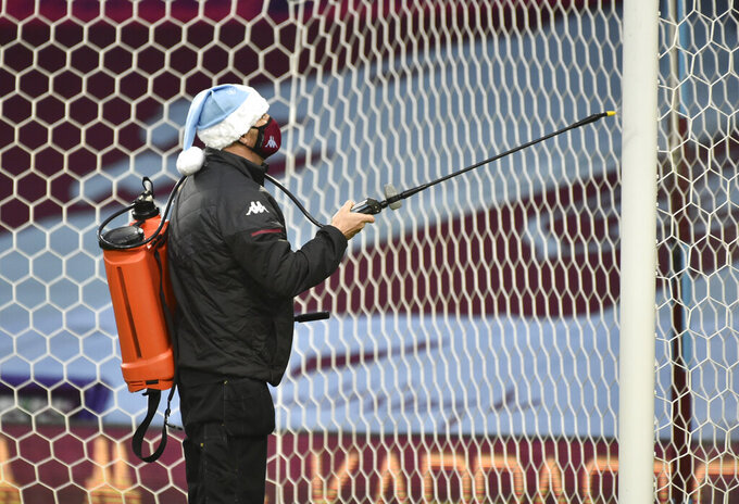 The goal post is sprayed with disinfectant before the English Premier League soccer match between Aston Villa and Crystal Palace at the Villa Park stadium in Birmingham, England, Saturday, Dec. 26, 2020.(AP Photo/Rui Vieira, Pool)