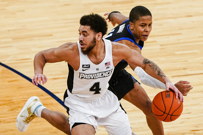 Providence's Jared Bynum (4) spins away from DePaul's Charlie Moore (11) during the second half of an NCAA college basketball game in the Big East conference tournament Wednesday, March 10, 2021, in New York. (AP Photo/Frank Franklin II)
