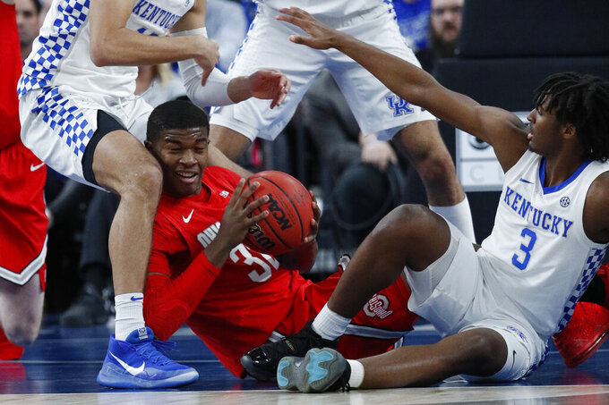 Ohio State's E.J. Liddell, left, and Kentucky's Tyrese Maxey (3) scramble for the ball during the first half of an NCAA college basketball game Saturday, Dec. 21, 2019, in Las Vegas. (AP Photo/John Locher)