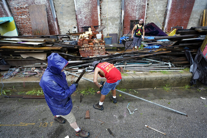 Larry Reed, left, Fred Williams, center, and Adrian Bentancourt clean up debris from a fence that was blown down by Hurricane Nicholas Tuesday, Sept. 14, 2021, in Galveston, Texas. (AP Photo/David J. Phillip)