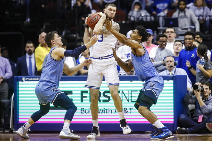 Seton Hall's Sandro Mamukelashvili, center, looks to pass against Villanova's Jermaine Samuels, right, and Collin Gillespie, left, during the first half of an NCAA college basketball game, Wednesday, March 4, 2020, in Newark, N.J. (AP Photo/John Minchillo)