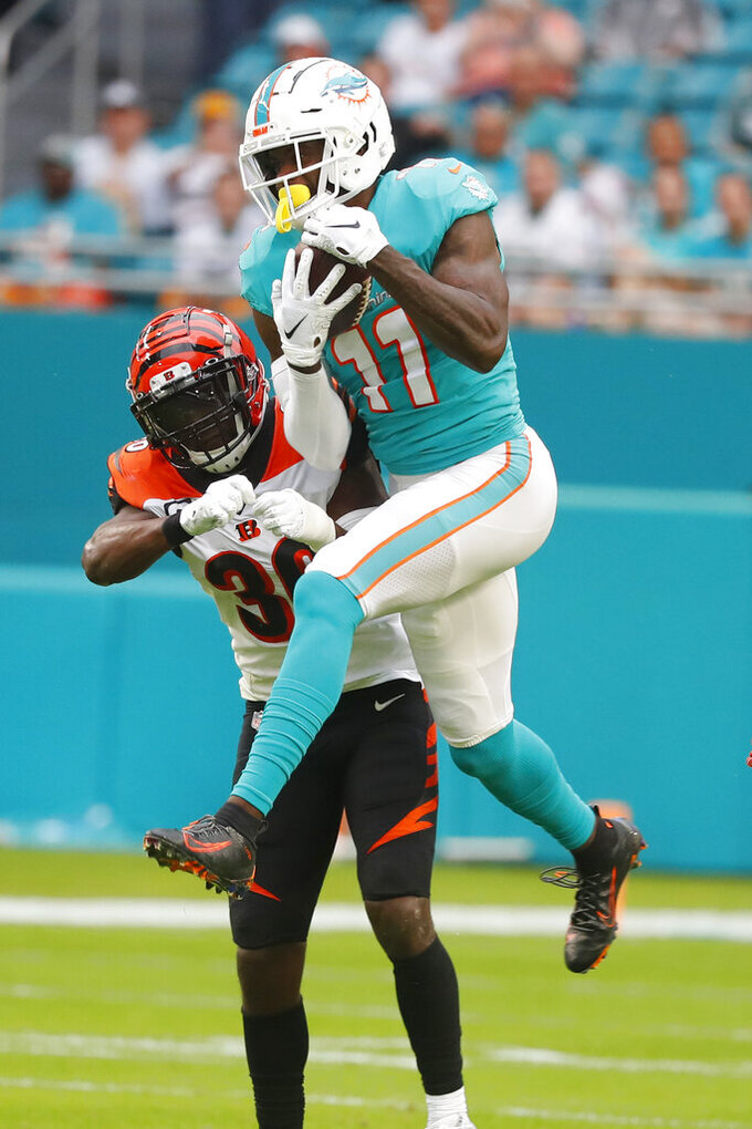 Miami Dolphins wide receiver DeVante Parker (11) catches a pass over Cincinnati Bengals strong safety Shawn Williams (36), during the first half at an NFL football game, Sunday, Dec. 22, 2019, in Miami Gardens, Fla. (AP Photo/Wilfredo Lee)