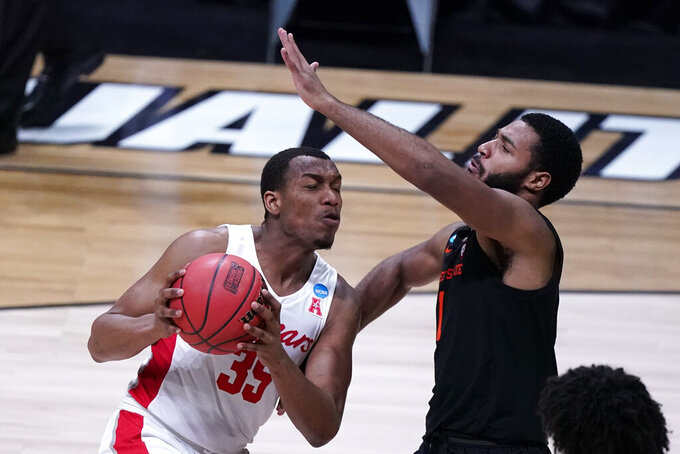 Houston forward Fabian White Jr. (35) drives on Oregon State forward Maurice Calloo, right, during the first half of an Elite 8 game in the NCAA men's college basketball tournament at Lucas Oil Stadium, Monday, March 29, 2021, in Indianapolis. (AP Photo/Michael Conroy)