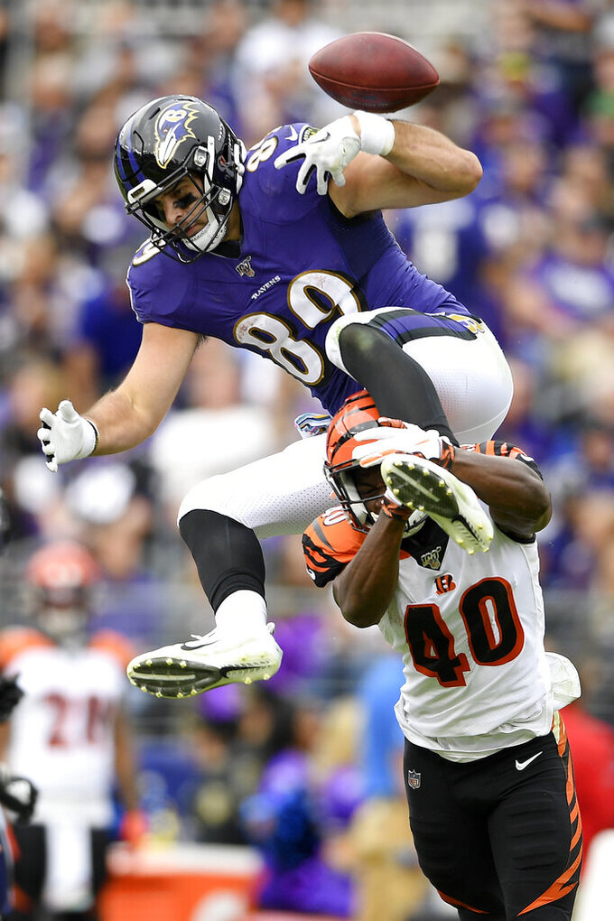Baltimore Ravens tight end Mark Andrews, top, fumbles the ball while trying to leap over Cincinnati Bengals defensive back Brandon Wilson (40) during the first half of a NFL football game Sunday, Oct. 13, 2019, in Baltimore. The Bengals recovered the fumble. (AP Photo/Nick Wass)