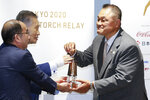 Japanese Olympic Committee President Yasuhiro Yamashita, right, receives the Olympic Flame from the Tokyo 2020 Organizing Committee President Yoshiro Mori, rear left, during the display ceremony at the Olympic Museum in Tokyo Monday, Aug. 31, 2020. The Olympic flame is going on display in Tokyo, just a short walk from the new National Stadium where it was supposed to be burning a month ago. (Rodrigo Reyes Marin/Pool Photo via AP)