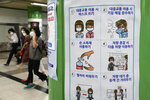 """People wearing face masks pass by a poster about precautions against the coronavirus at a subway station in Seoul, South Korea, Tuesday, July 13, 2021. South Korea's streak of more than 1,000 daily coronavirus cases has reached a week as health authorities scramble to slow a viral surge that has brought Seoul's thriving nightlife to a standstill and professional baseball to a halt. The signs on posters read """"Rules of using public transport."""" (AP Photo/Ahn Young-joon)"""