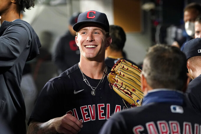 Cleveland Indians starting pitcher Zach Plesac smiles as he greets teammates in the dugout after the seventh inning of the team's baseball game against the Seattle Mariners on Thursday, May 13, 2021, in Seattle. (AP Photo/Elaine Thompson)