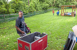 Rev. Michael Day goes though a container of audio equipment to set up for worship service on Wednesday, Aug. 18, 2021, in Northview Heights in Pittsburgh. making it his mission to work with the city and group violence outreach workers to address the needs of families in Northview Heights. He and church members planned to set up a tent in the neighborhood and try to connect residents to counseling, basic necessities and church ministries. (Ben Braun/Pittsburgh Post-Gazette via AP)