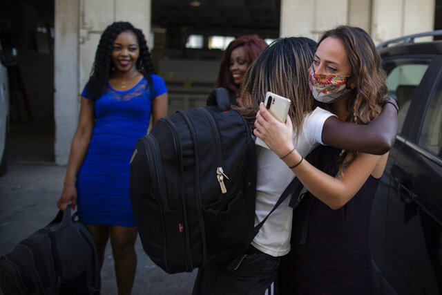 "Déa Hage-Chahine, right, hugs a Kenyan migrant outside a shelter where she had been staying with other migrants, in Mkalles, Lebanon, Friday, Oct. 9, 2020. Hage-Chahine and Serge Majdalani are two young Lebanese on a mission to repatriate migrant workers who have been stranded in Lebanon amid the worst economic crisis in the country's modern history. In two months, they have sent more than 120 women, mostly Kenyans and some Ethiopians, back home, fundraising more than $35,000 for flights and coronavirus tests through a ""gofundme"" online campaign. (AP Photo/Hassan Ammar)"