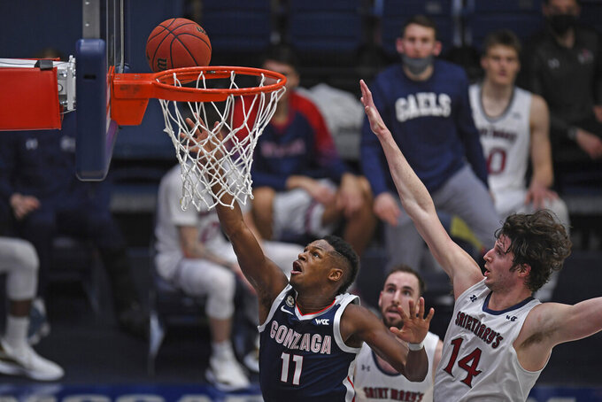 Gonzaga's Joel Ayayi (11) makes a basket past Saint Mary's Kyle Bowen (14) during the first half of an NCAA college basketball game in Moraga, Calif., Saturday, Jan. 16, 2021. (Jose Carlos Fajardo/Bay Area News Group via AP)