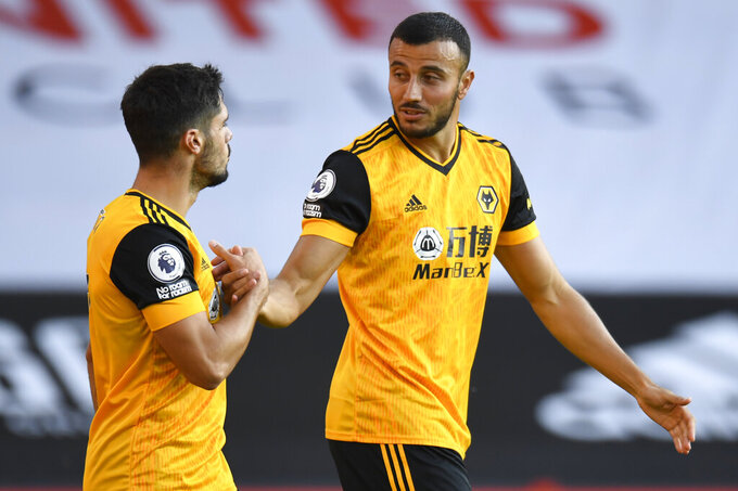 Wolverhampton Wanderers' Romain Saiss, right, celebrates scoring his sides second goal during the English League Cup soccer match between Sheffield United and Wolves at Bramall Lane stadium in Sheffield, England, Monday, Sept. 14, 2020. (Peter Powell/Pool via AP)