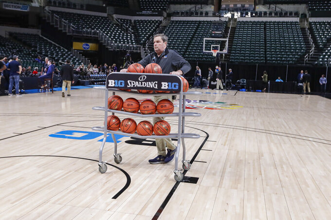 Basketballs are removed from the court at Bankers Life Fieldhouse, in Indianapolis, Thursday, March 12, 2020, after the Big Ten Conference announced that remainder of the men's NCAA college basketball games tournament was cancelled. (AP Photo/Michael Conroy)