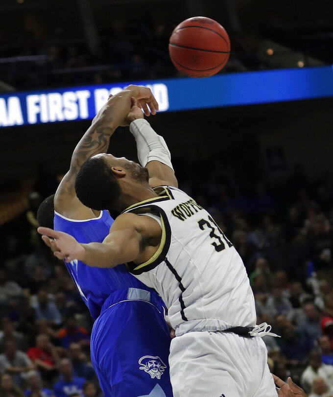 Seton Hall's Shavar Reynolds, left, and Wofford's Donovan Theme-Love go after a rebound during the first half of a first-round game in the NCAA men's college basketball tournament in Jacksonville, Fla., Thursday, March 21, 2019. (AP Photo/John Raoux)