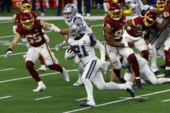 Dallas Cowboys running back Ezekiel Elliott (21) carries the ball as Washington Football Team's Cole Holcomb (55) and Chase Young (99), right, give chase in the second half of an NFL football game in Arlington, Texas, Thursday, Nov. 26, 2020. (AP Photo/Roger Steinman)