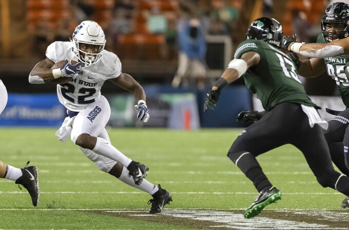 Utah State running back Eltoro Allen (22) cuts back as Hawaii defensive back Khoury Bethley (13) attempts to track him down in the second half of an NCAA college football game, Saturday, Nov. 3, 2018, in Honolulu. Utah beat Hawaii 56-17. (AP Photo/Eugene Tanner)