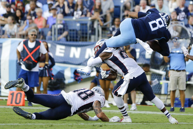 Tennessee Titans quarterback Marcus Mariota (8) scores a 2-point conversion against New England Patriots defenders Calvin Munson (48) and Duron Harmon (21) in the first half of a preseason NFL football game Saturday, Aug. 17, 2019, in Nashville, Tenn. (AP Photo/James Kenney)