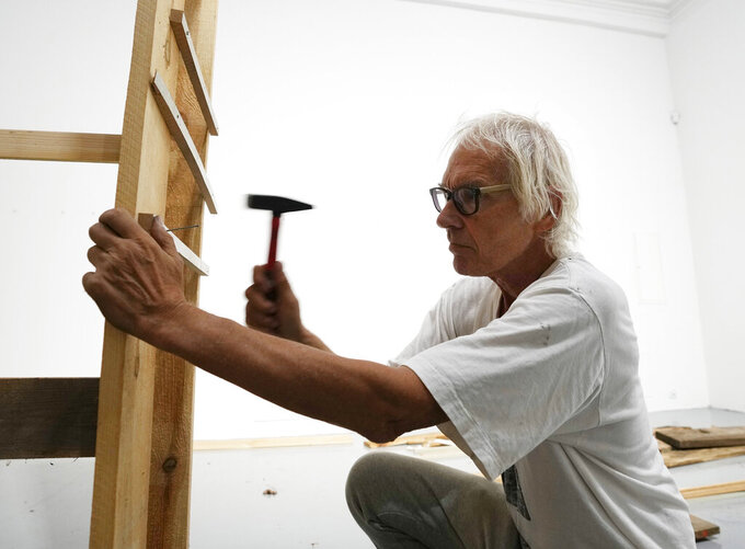"""Lars Vilks, a Swedish artist, constructs an exhibit at the Ujazdowski Castle Center for Contemporary Art in Warsaw, Poland, Wednesday Aug. 25, 2021. The exhibition which opens Friday at the Polish state museum features the works of provocative artists in what organizers describe as a celebration of free speech, and a challenge to political correctness and """"cancel culture"""" on the political left. Some critics, however, accuse the organizers of the show titled """"Political Art"""" of giving a platform to anti-Semitic, racist and Islamophobic messages. Vilks lives under police protection for making a drawing of a dog with the head of the Prophet Muhammed. The drawing enraged many Muslims in 2007 and sparked death threats from extremists. (AP Photo/Czarek Sokolowski)"""
