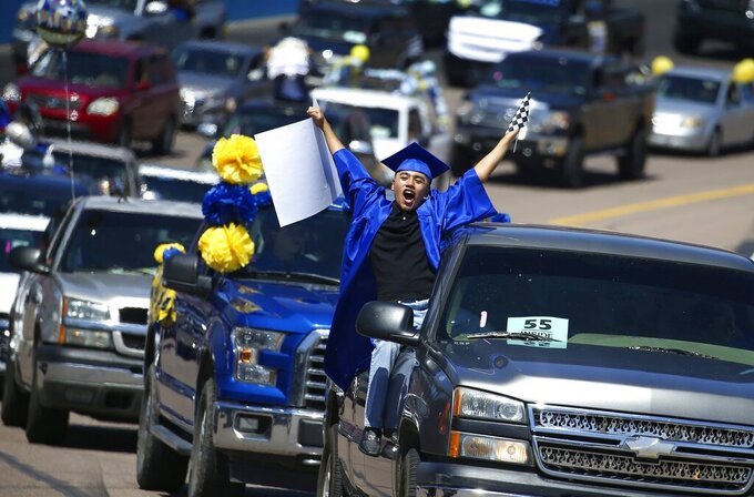 Jaime Susano, a graduating senior from Buckeye Union High School, shouts in celebration during a drive-thru graduation ceremony Parade of Graduates on the race track at Phoenix Raceway, Saturday, May 16, 2020, in Avondale, Ariz. The coronavirus has caused most schools to either cancel traditional graduations or find alternative celebrations. (AP Photo/Ross D. Franklin)