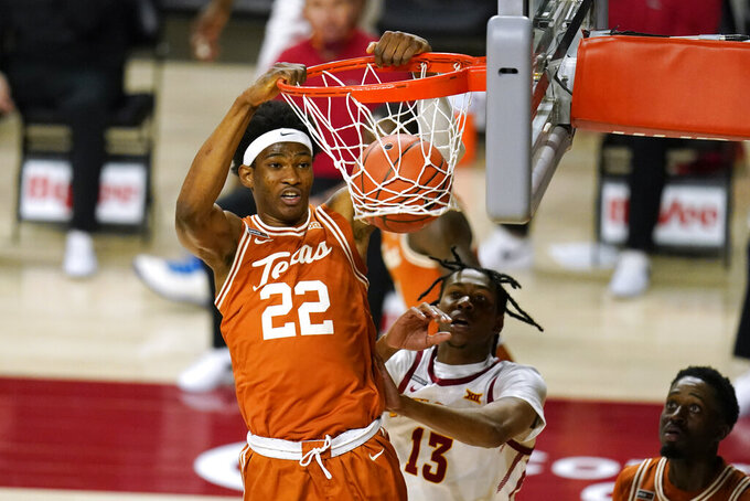 Texas forward Kai Jones (22) dunks the ball ahead of Iowa State forward Javan Johnson (13) during the first half of an NCAA college basketball game, Tuesday, March 2, 2021, in Ames, Iowa. (AP Photo/Charlie Neibergall)
