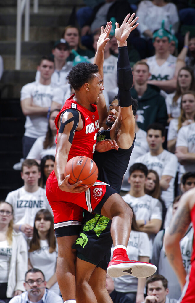 Ohio State's Musa Jallow, left, dishes off against Michigan State's Kenny Goins during the first half of an NCAA college basketball game, Sunday, Feb. 17, 2019, in East Lansing, Mich. (AP Photo/Al Goldis)