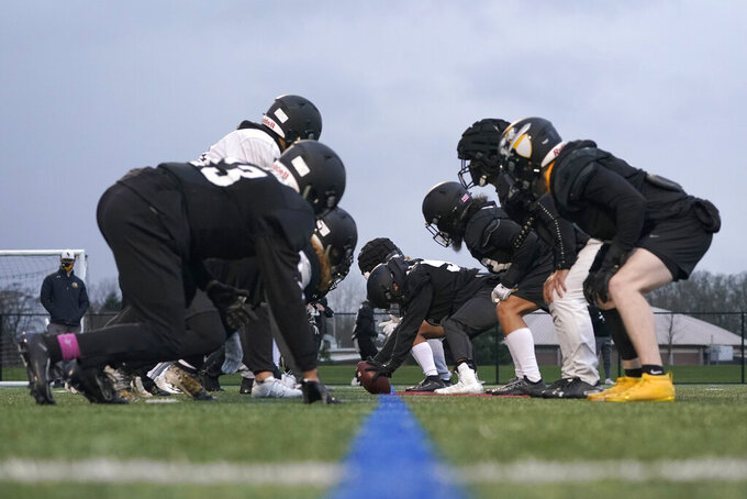 FILE- In this Tuesday, Feb. 2, 2021, file photo, Pacific Lutheran football players wait for the snap on the line of scrimmage during practice in Tacoma, Wash. Are you ready for some (more) football! No need to take a break from the gridiron just because the NFL season is over. Lower-division college teams are ready to kick off their seasons -- snow-covered fields and all -- after sitting out the fall because of the pandemic.  (AP Photo/Ted S. Warren, File)