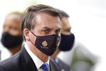 FILE - In this May 18, 2020, file photo, Brazilian President Jair Bolsonaro wears a mask due to the coronavirus pandemic as he talks with supporters upon departure from his official residence, Alvorada palace, in Brasilia, Brazil. The logo on the mask reads