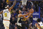 San Antonio Spurs guard Derrick White, middle, shoots between Golden State Warriors center Willie Cauley-Stein (2) and forward Draymond Green (23) during the first half of an NBA basketball game in San Francisco, Friday, Nov. 1, 2019. (AP Photo/Jeff Chiu)