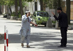 An injured man talking on his mobile phone is questioned by a security officer after an explosion in Kabul, Afghanistan, Wednesday, May 8, 2019. The Taliban attacked the offices of an international NGO, called Counterpart International, in the Afghan capital, setting off a huge explosion and battling Afghan security forces in an assault that wounded at least nine people, officials said. (AP Photo/Rahmat Gul)