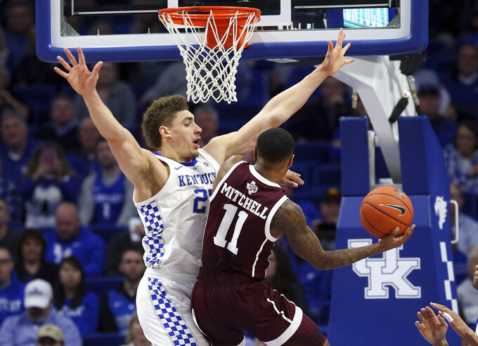 Texas A&M's Wendell Mitchell (11) shoots under pressure from Kentucky's Reid Travis during the second half of an NCAA college basketball game in Lexington, Ky., Tuesday, Jan. 8, 2019. Kentucky won 85-74. (AP Photo/James Crisp)
