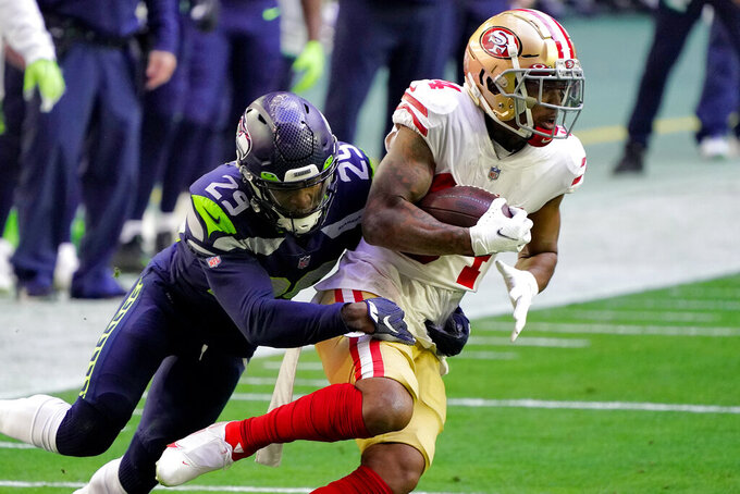 San Francisco 49ers wide receiver Kendrick Bourne is tackled by Seattle Seahawks free safety D.J. Reed (29) during the first half of an NFL football game, Sunday, Jan. 3, 2021, in Glendale, Ariz. (AP Photo/Rick Scuteri)