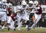 Connecticut running back Kevin Mensah (34) runs in for a touchdown as Massachusetts cornerback Elijah Johnson (27) tries to pull him down during the first half of an NCAA college football game, Saturday, Oct. 26,, 2019, in Amherst, Mass. (AP Photo/Jessica Hill)