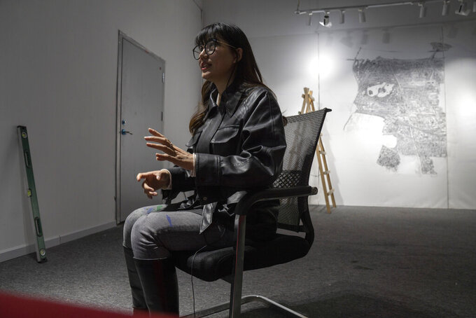 Chinese artist Yang Qian speaks during an interview at her studio in Wuhan in central China's Hubei province on Sunday, Jan. 24, 2021. Yang, who worked as a volunteer delivering vital supplies to hospitals and residents during the city's pandemic 76-day lockdown, is using her art work to make sure that history is not forgotten. (AP Photo/Ng Han Guan)