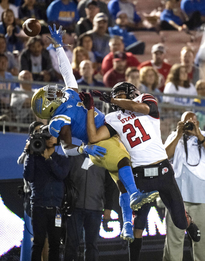 UCLA defensive back Darnay Holmes, left, can't intercept a pass intended to Utah wide receiver Solomon Enis during the first half of an NCAA college football game Friday, Oct. 26, 2018, in Pasadena, Calif. (AP Photo/Kyusung Gong)
