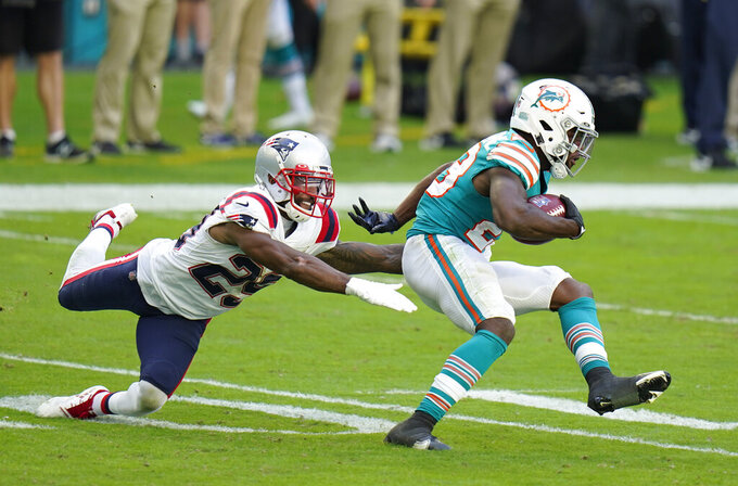 New England Patriots defensive back Justin Bethel (29) dives at Miami Dolphins' Noah Igbinoghene (23) during the second half of an NFL football game Sunday, Dec. 20, 2020, in Tampa, Fla. (AP Photo/Chris O'Meara)