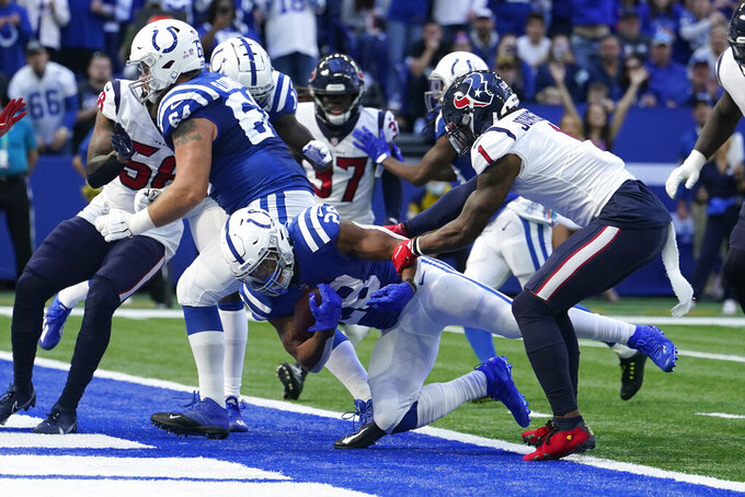 Indianapolis Colts' Jonathan Taylor (28) rushes for a touchdown against Houston Texans' Lonnie Johnson (1) during the second half of an NFL football game, Sunday, Oct. 17, 2021, in Indianapolis. (AP Photo/Michael Conroy)