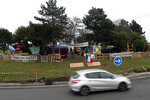 Protestors wearing yellow vests occupy a makeshift camp in a roundabout near Senlis, north of Paris, Thursday, Jan. 10, 2019. With its makeshift grocery, camp beds and community spirit, the large central island about 60 kilometers north of Paris has been transformed over the past two months into an encampment where dozens of yellow vests protesters gather day in day out to organize their long-standing fight against the French government. (AP Photo/Thibault Camus)