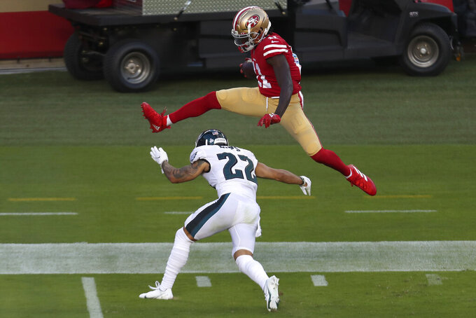 San Francisco 49ers wide receiver Brandon Aiyuk, top, jumps over Philadelphia Eagles safety Marcus Epps (22) to score on a touchdown run during the first half of an NFL football game in Santa Clara, Calif., Sunday, Oct. 4, 2020. (AP Photo/Jed Jacobsohn)