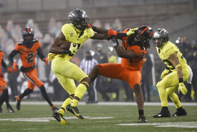Oregon wide receiver Devon Williams (2) skirts around Oregon State inside linebacker Avery Roberts (34) during the second half of an NCAA college football game in Corvallis, Ore., Friday, Nov. 27, 2020. Oregon State won 41-38. (AP Photo/Amanda Loman)