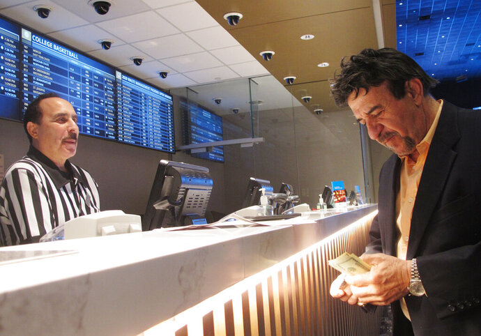 In this Jan. 29, 2020 photo, a man makes a bet on the upcoming Super Bowl at Bally's casino in Atlantic City, N.J. Business was brisk at sports books around the country on Super Bowl Sunday, with customers risking money on everything from the coin toss at the start of the game, to the color of the Gatorade dumped on the winning coach, Kansas City's Andy Reid, at the end of it. (AP Photo/Wayne Parry)