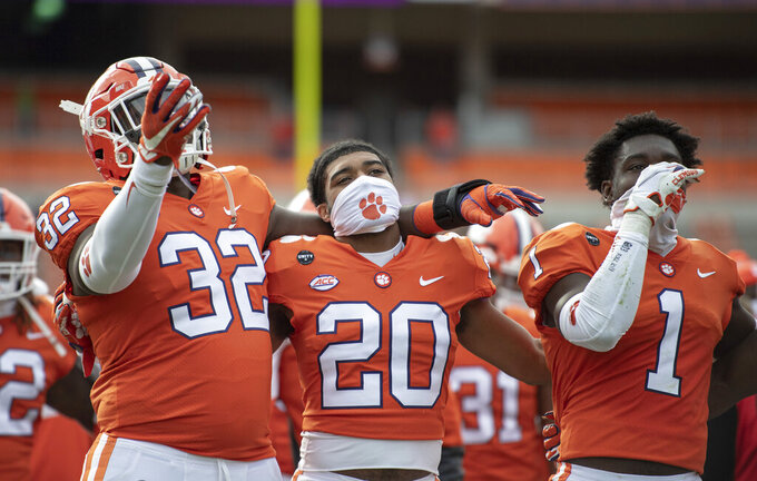 Clemson defensive tackle Etinosa Reuben (32), cornerback LeAnthony Williams (20), and cornerback Derion Kendrick (1) sing the alma mater after an NCAA college football game against Boston College Saturday, Oct. 31, 2020, in Clemson, S.C. (Josh Morgan/Pool Photo via AP)